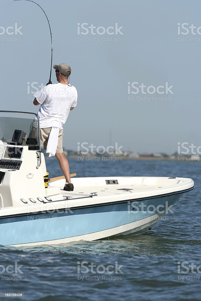 Fisherman Reeling in a Fish from his Boat royalty-free stock photo