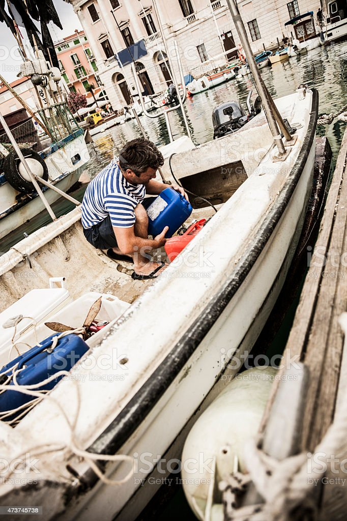 Fisherman refill the tank before leaving from the harbor stock photo