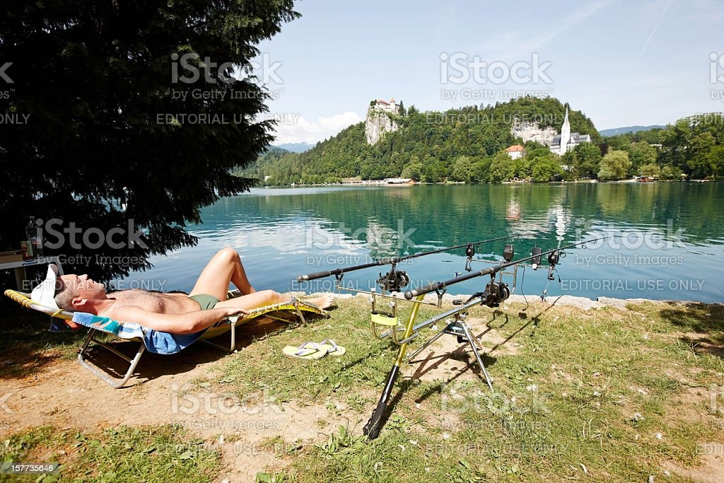 Fisherman relaxing on shore of Lake Bled stock photo