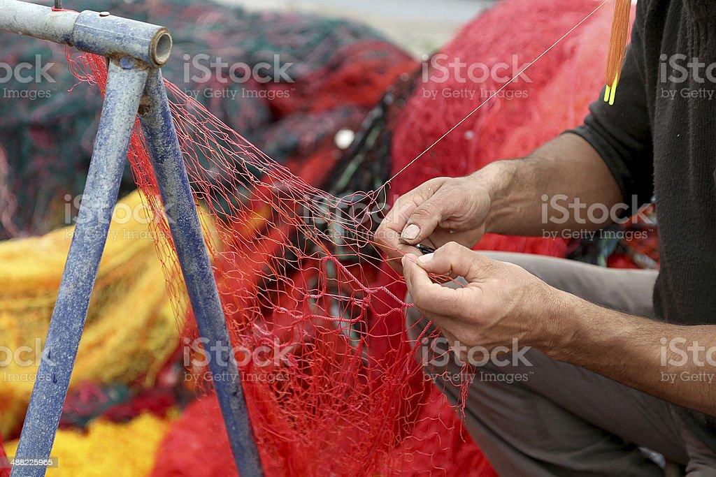 Fisherman Repairs Fishing Net stock photo