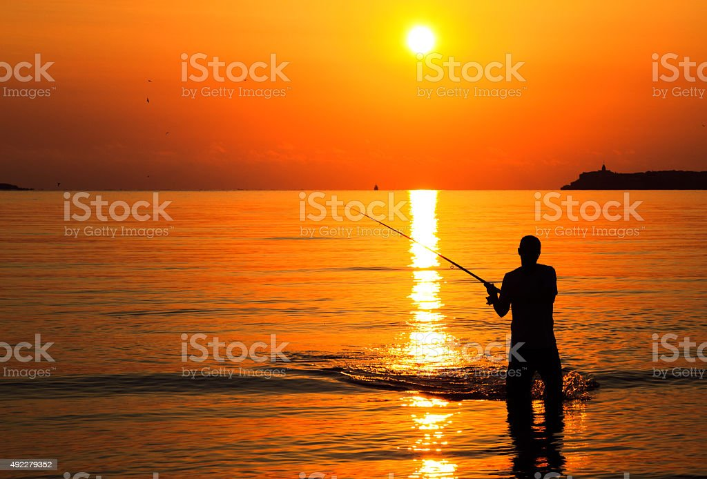 Fisherman silhouette at sunrise stock photo