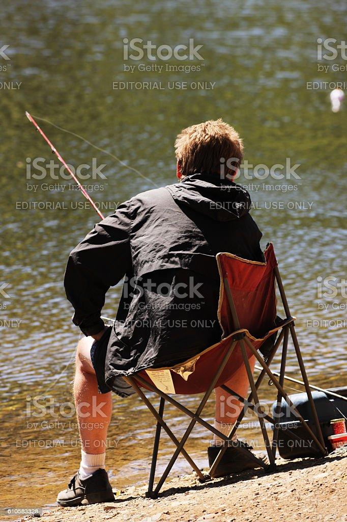 Fisherman Sits Holding Fishing Rod Watching Bobber stock photo