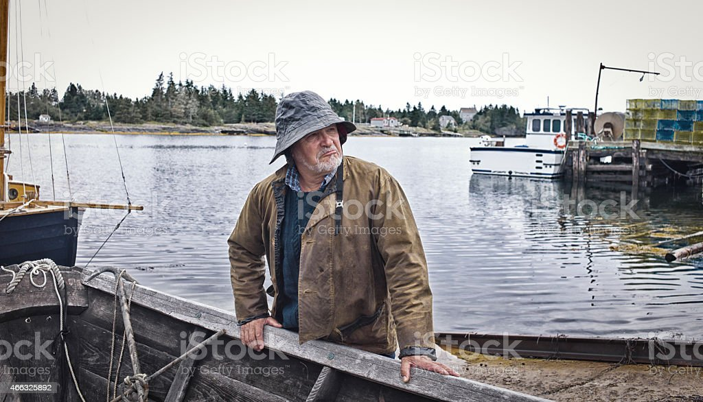 Fisherman Standing Near a Dory, Mahone Bay, Nova Scotia stock photo