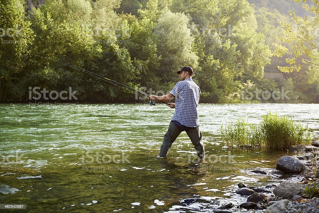 Fisherman standing near river and holding fishing rod stock photo