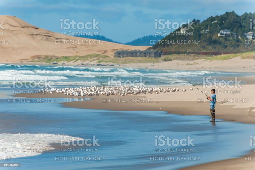 Fisherman surf fishes along the shores of Pacific City stock photo