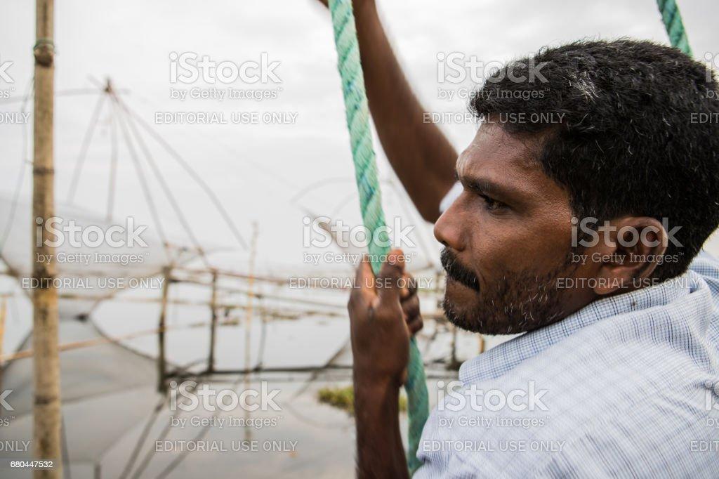 Fisherman tends to his net in Kerala, India. stock photo