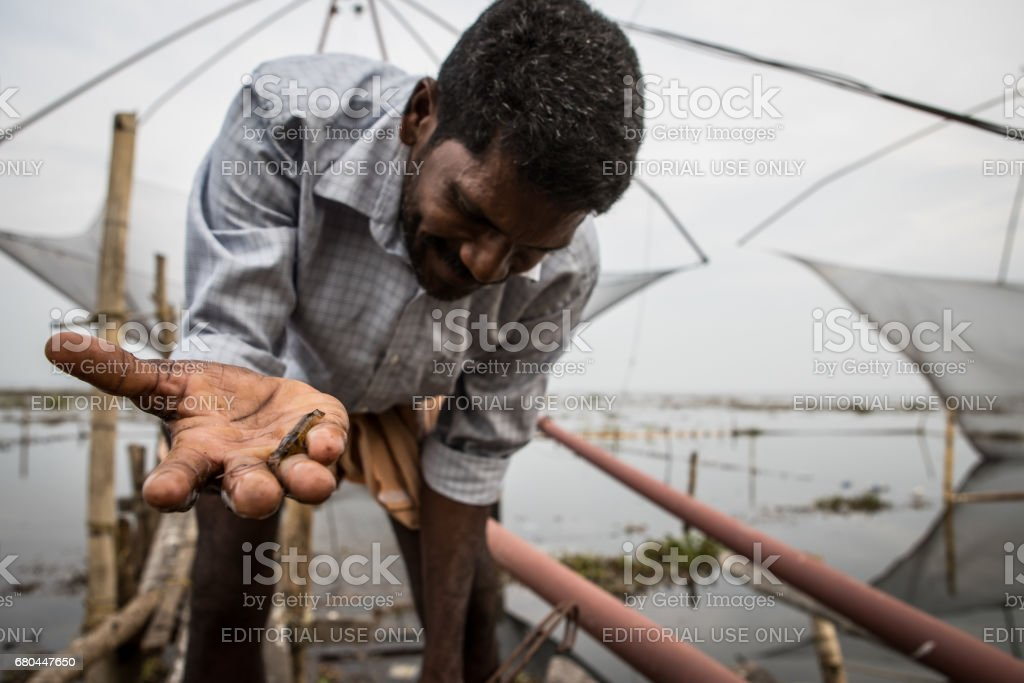 Fisherman tends to his net in Kerala, India. stock photo