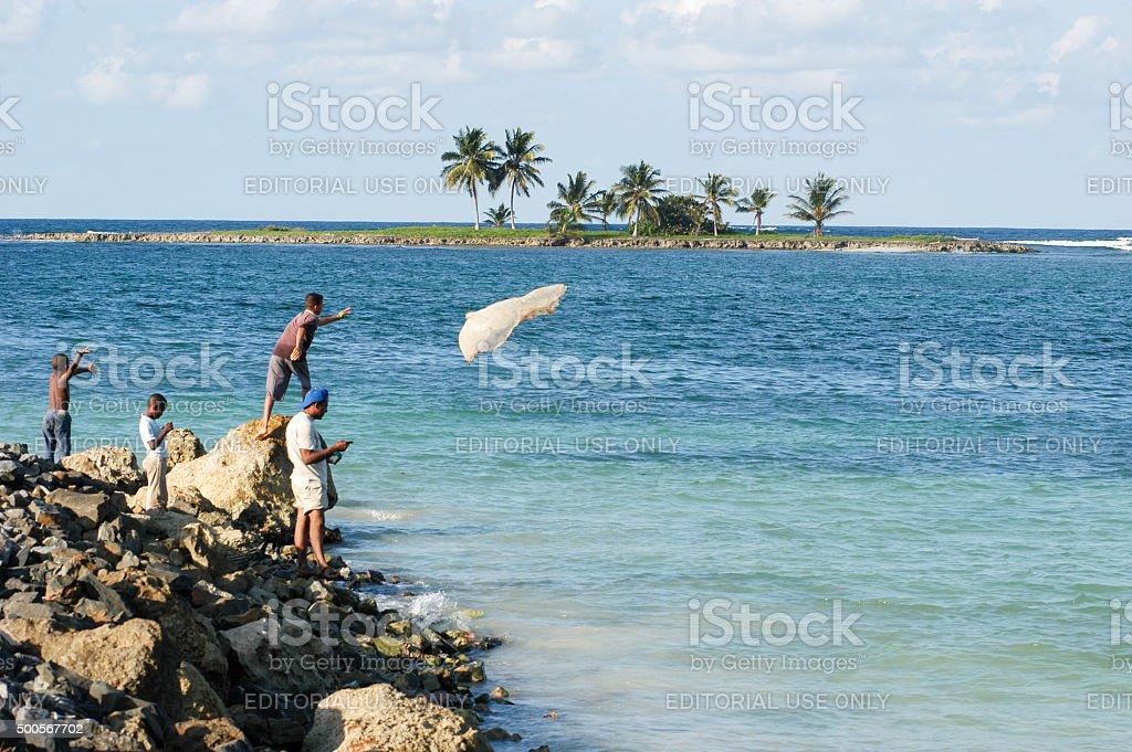Fisherman throwing a fishing net into the sea stock photo