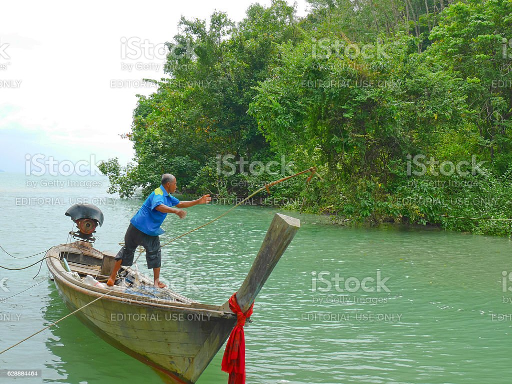 Fisherman throws anchor into the sea at high tide stock photo