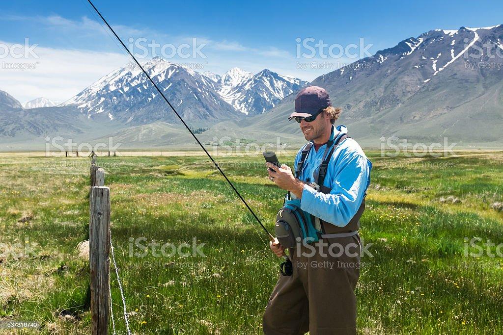 Fisherman Using His Phone In A Beautiful Mountain Meadow stock photo