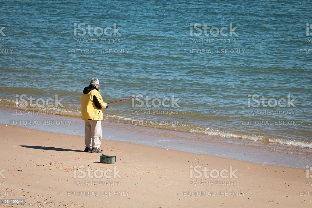 fisherman walking on the edge of the ocean stock photo