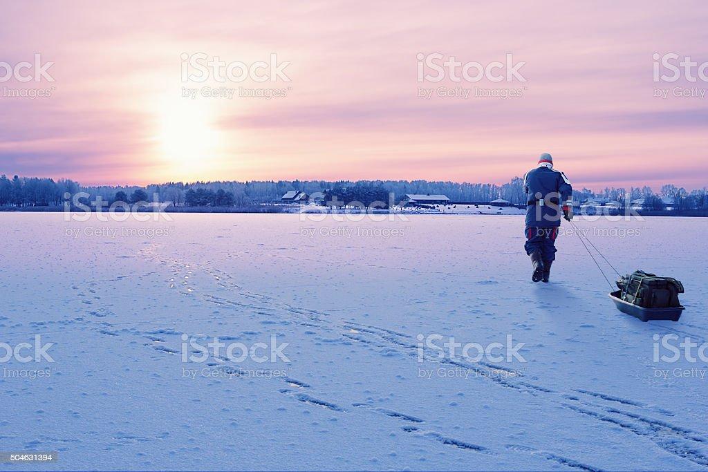 Fisherman walking on the frozen lake stock photo