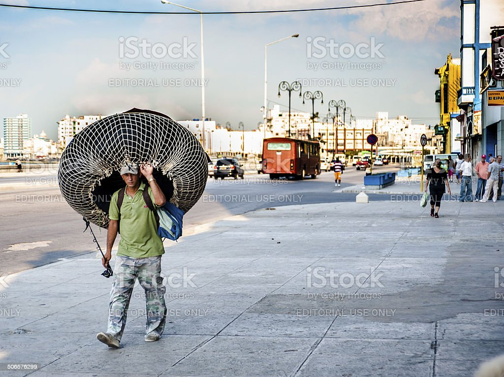 Fisherman walking with rubber tire-like raft on head stock photo