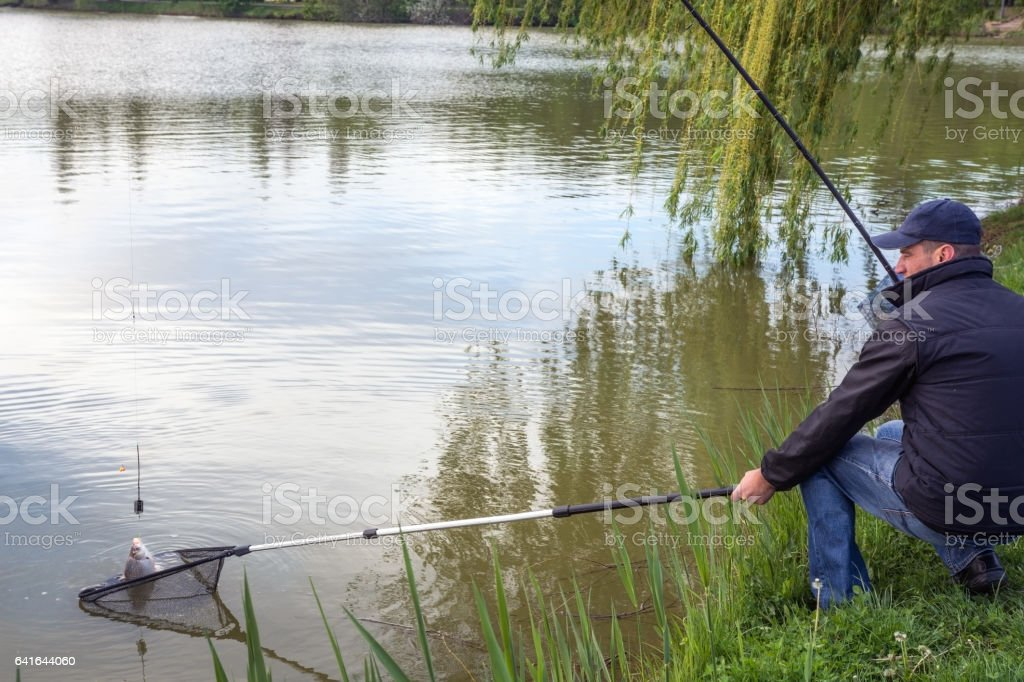 Fisherman who catch fish in the lake, in spring stock photo