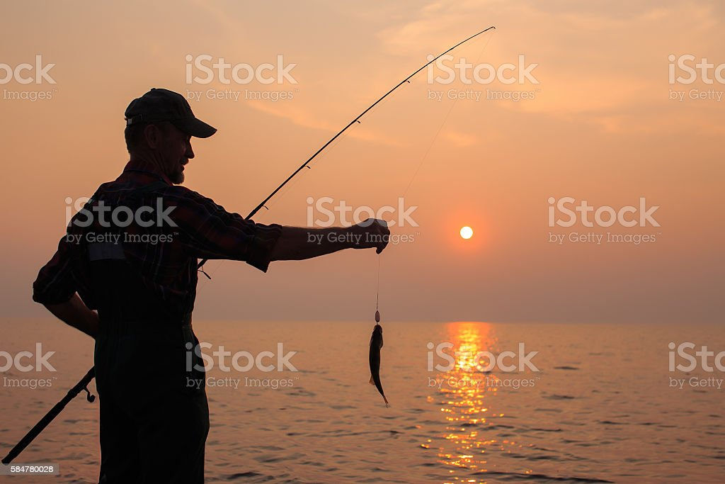 fisherman with a catch at sunset stock photo