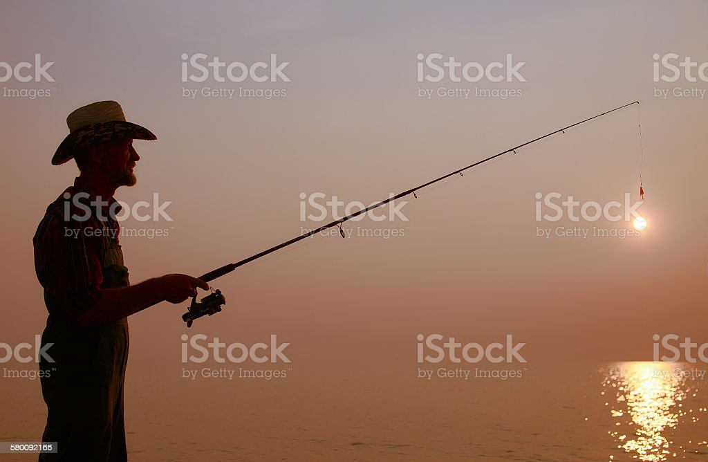 fisherman with a fishing rod on the background of sunset stock photo
