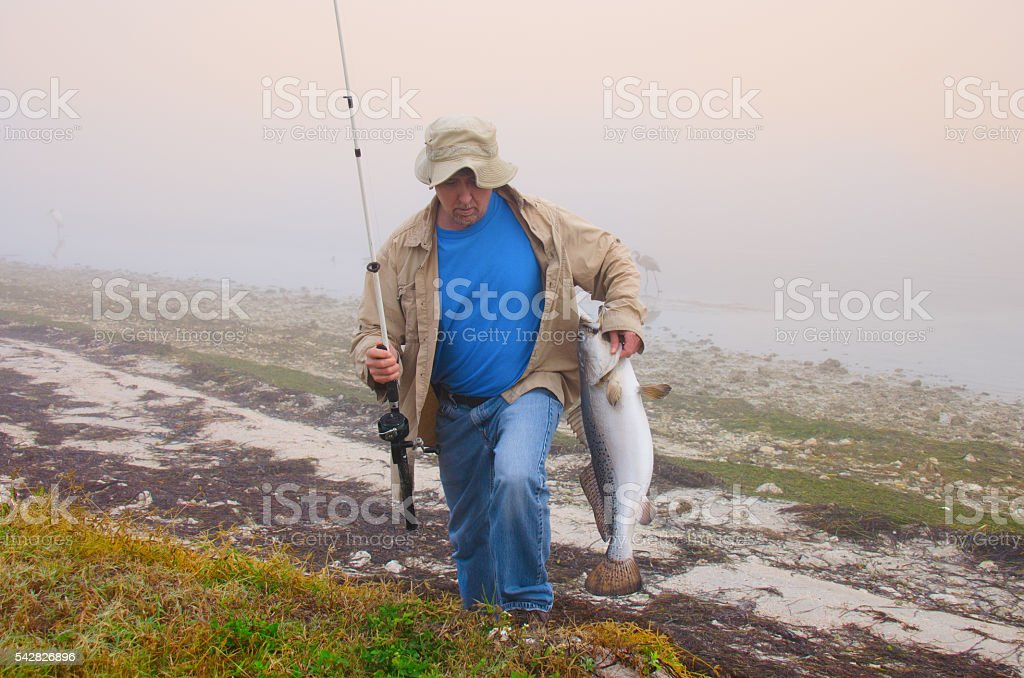 Fisherman with a huge fish he caught on a foggy morning stock photo
