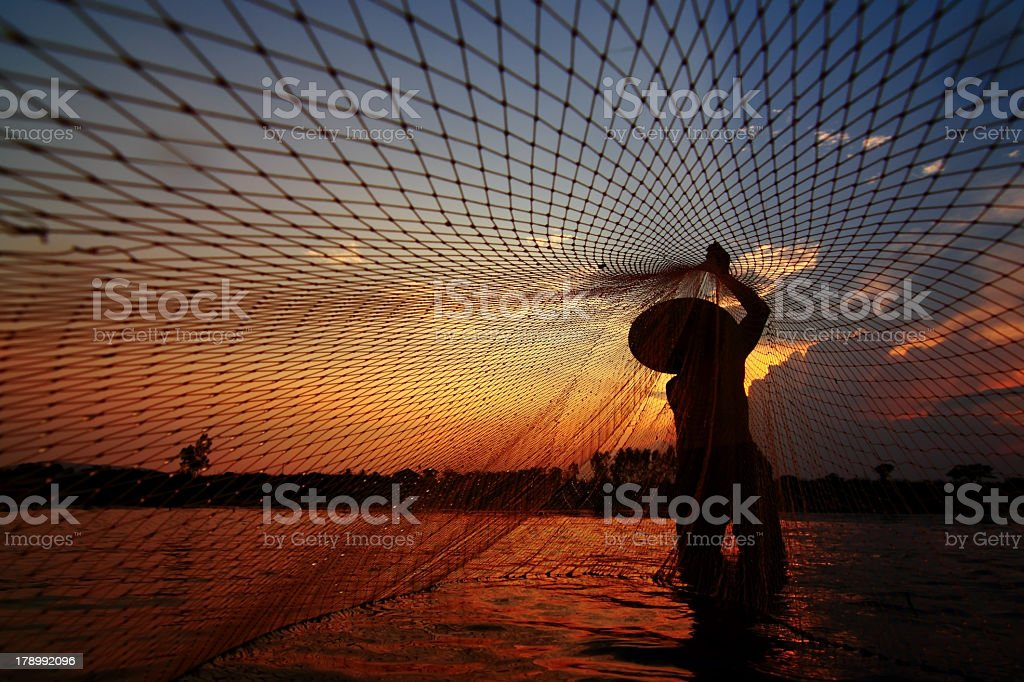 Fisherman with a net in the Mekong River stock photo