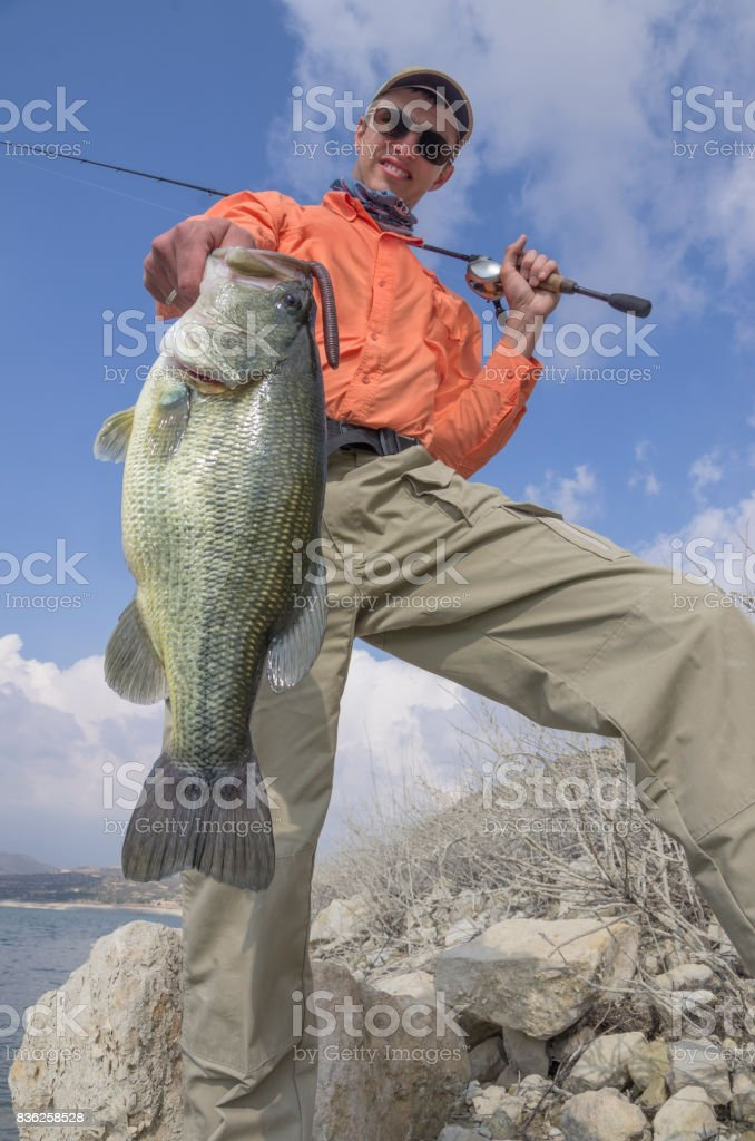 Fisherman with bass trophy stock photo