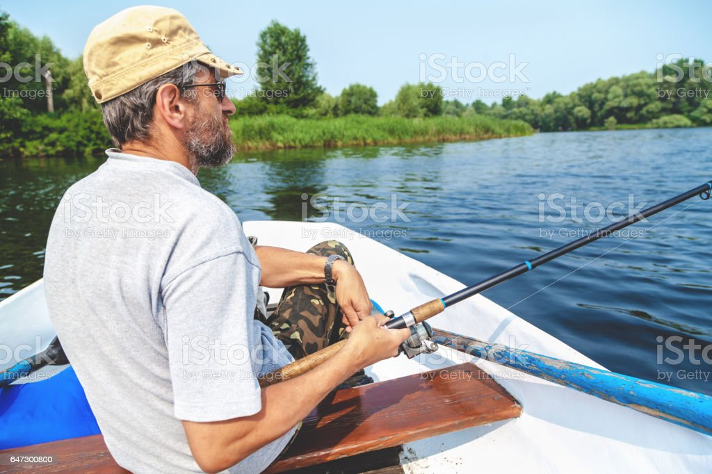 Fisherman with beard sitting in boat and holding fishing rod stock photo