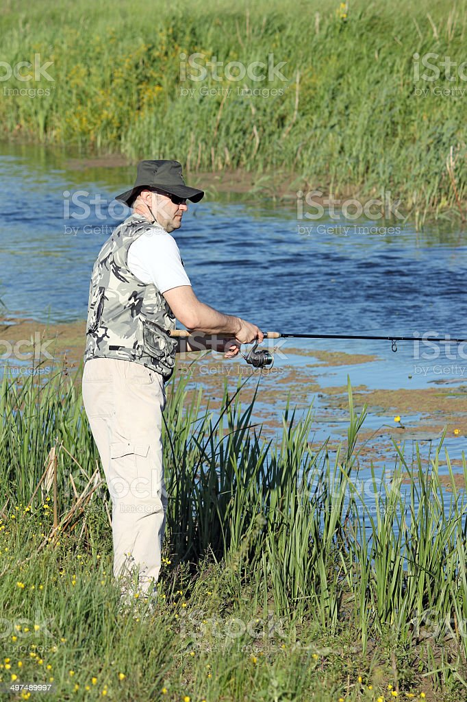 fisherman with fishing rod on river royalty-free stock photo