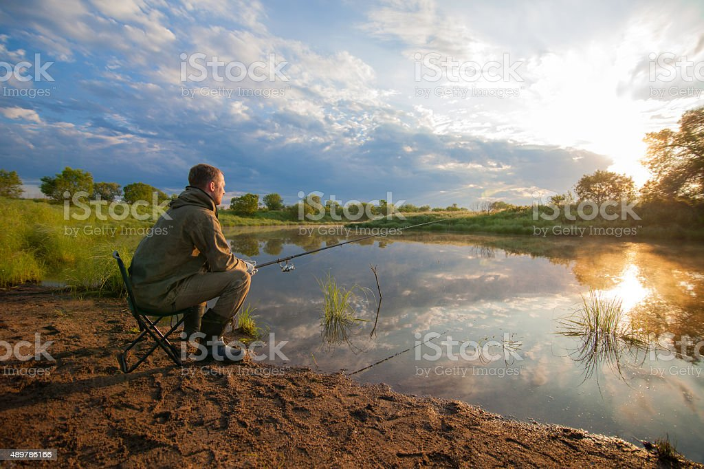 Fisherman with fish-rod in his hands near a pond stock photo