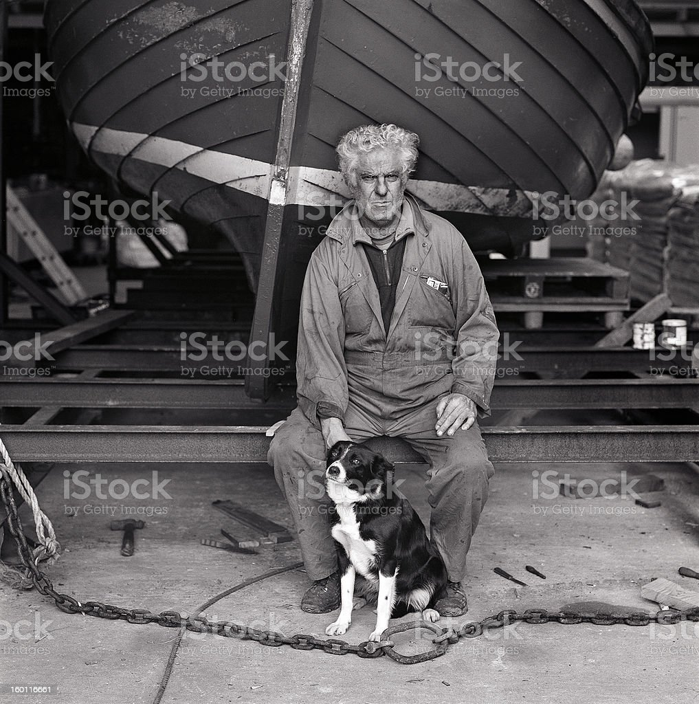 Fisherman with sheepdog and boat in boatshed royalty-free stock photo