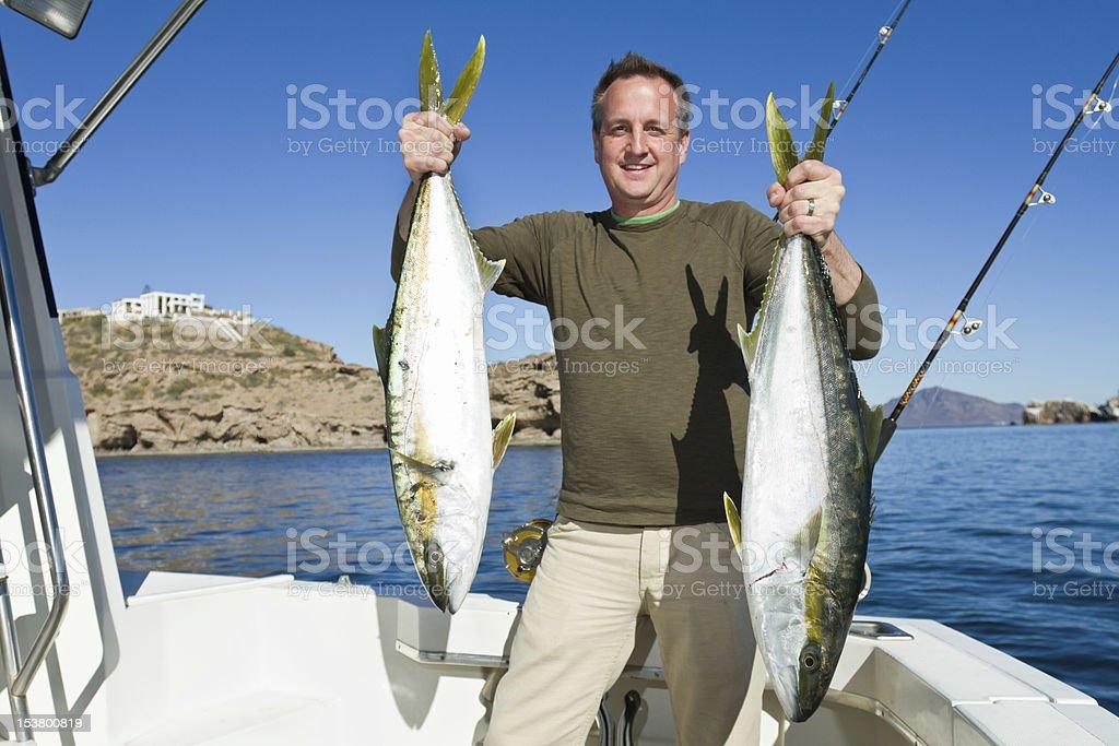 Fisherman with Tuna or Yellow Tail Mackeral Fish stock photo