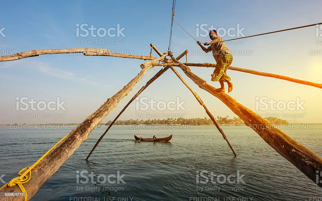 Fisherman works Chinese fishing net, Fort Kochi, Kerala, India. stock photo