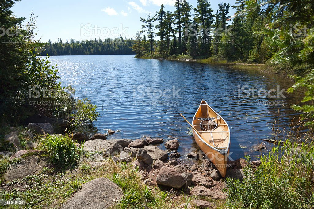 Fisherman's canoe on rocky shore in northern Minnesota lake stock photo