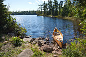 Fisherman's canoe on rocky shore in northern Minnesota lake