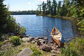 Fisherman's canoe on rocky shore in northern Minnesota lake