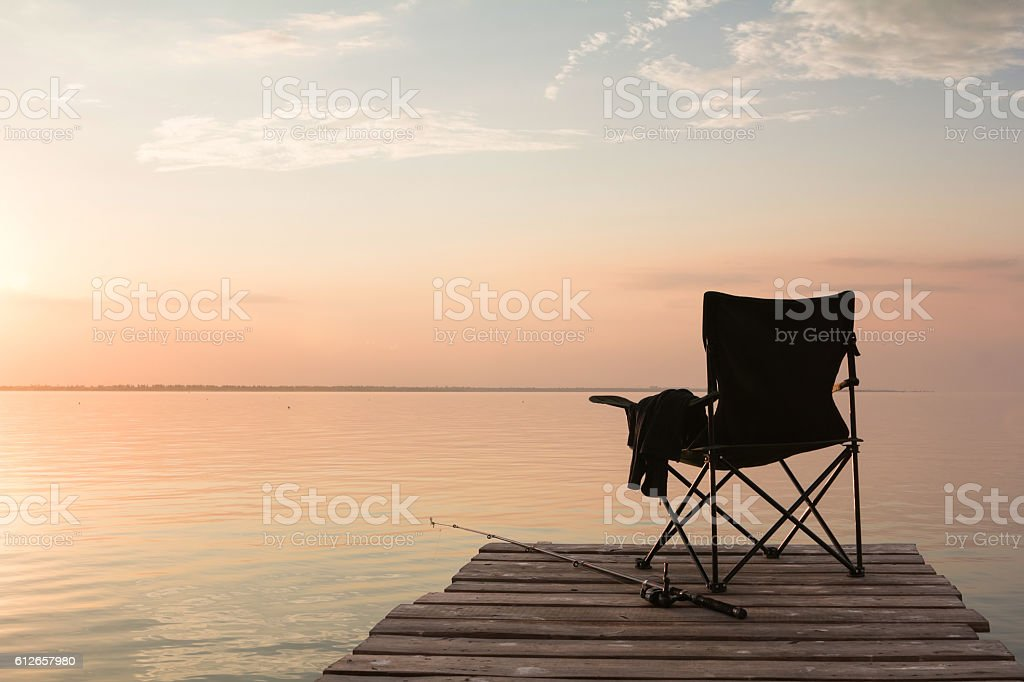 fisherman's chair over the lake at sunset stock photo