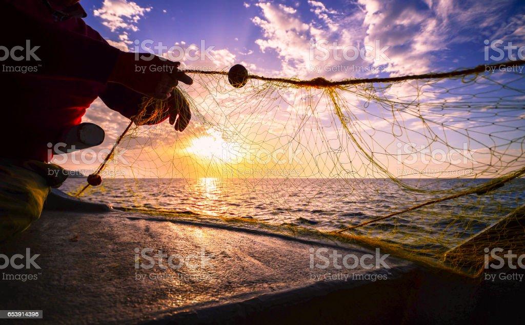 Fisherman's hand silhouette  throwing fishing net at sunset, Crete, Greece stock photo