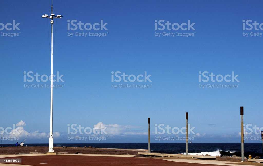 Fishermen and Lightpole on Pier at Beach royalty-free stock photo