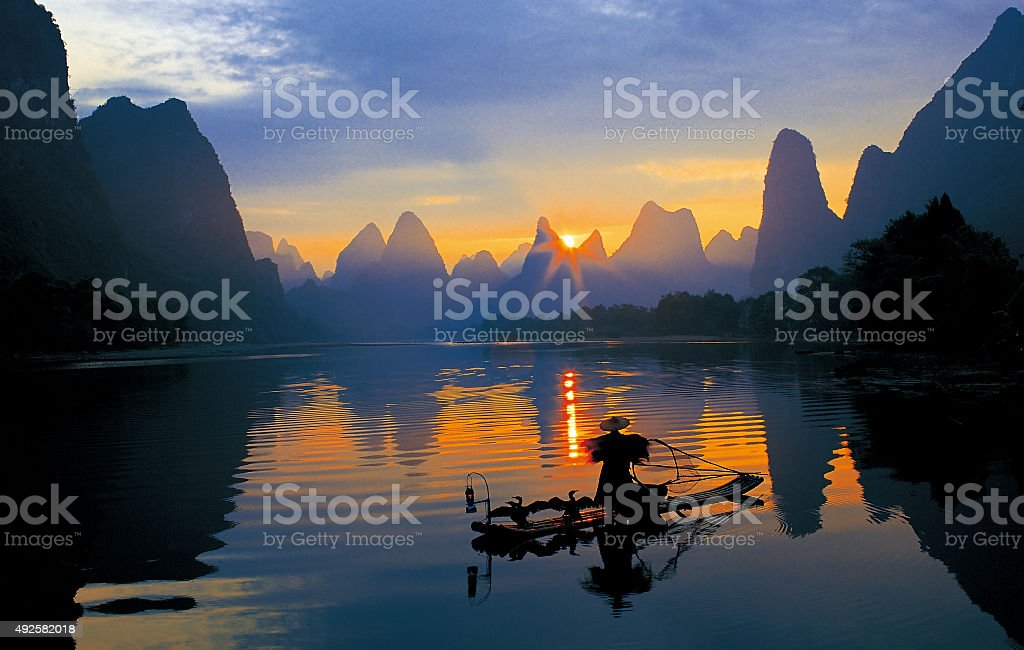 Fishermen and osprey in Li River stock photo