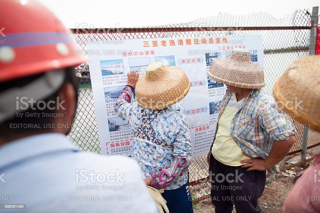 Fishermen and women reading sign in Sanya, China stock photo
