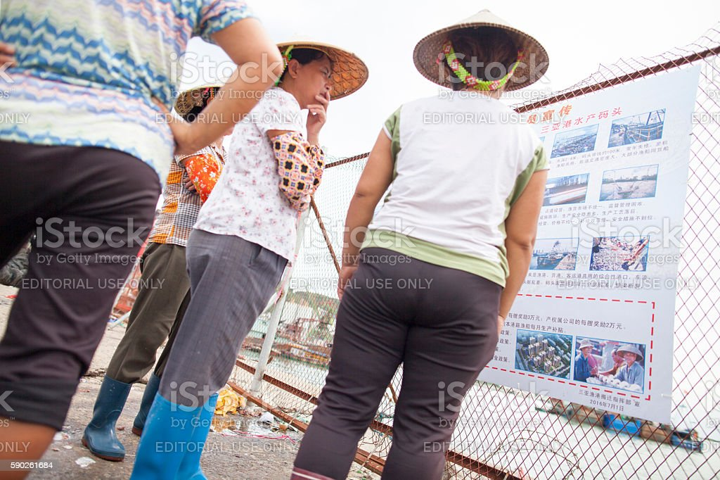 Fishermen and women reading sign in Sanya, China stock photo