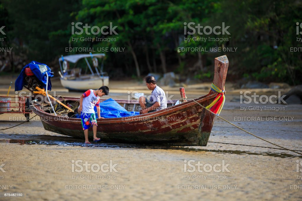 Phuket, Thailand - April 13, 2016: Fishermen are checking boats for fishing at sea time. stock photo
