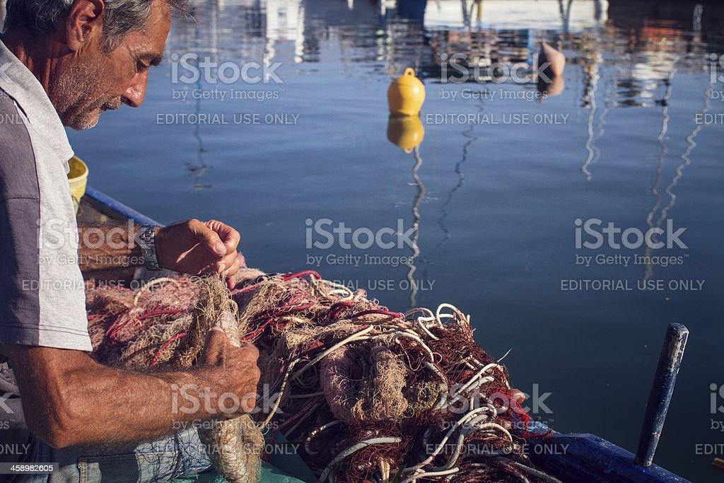 Fishermen at work, by the Harbor of Alghero, Sardinia, Italy royalty-free stock photo