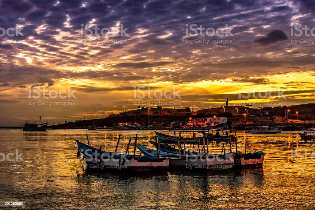 Fishermen boats at sunset in a tropical island. People bowing. stock photo