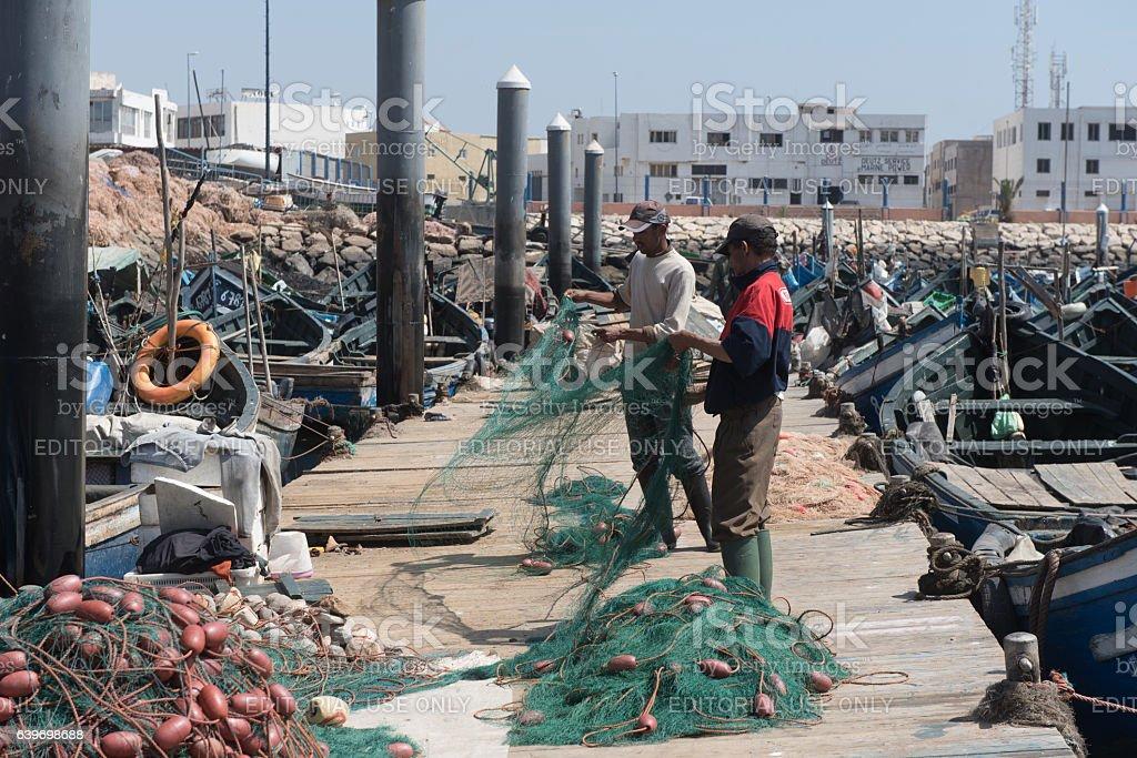 Fishermen cleaning seine stock photo