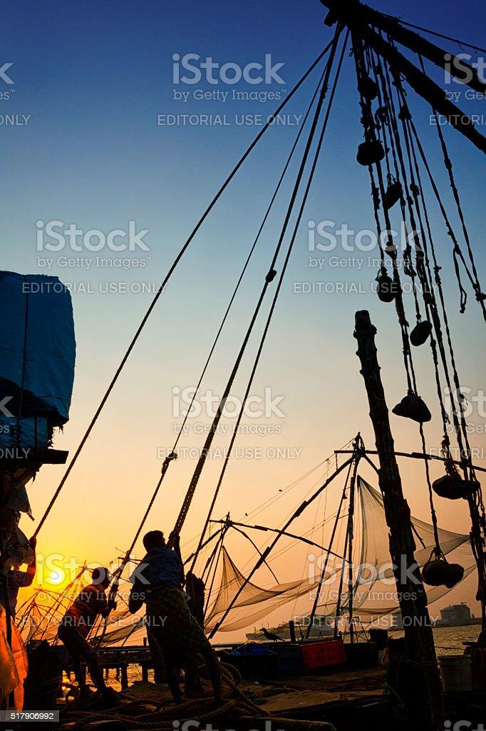 Fishermen hauling net at sunset in Kochi, India stock photo