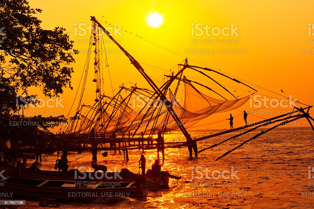 Fishermen hauling net at sunset in Kochi, India stock photo