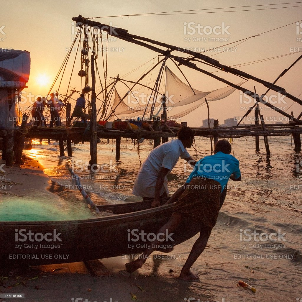 Fishermen hauling nets and launching boat in Kochi, India stock photo