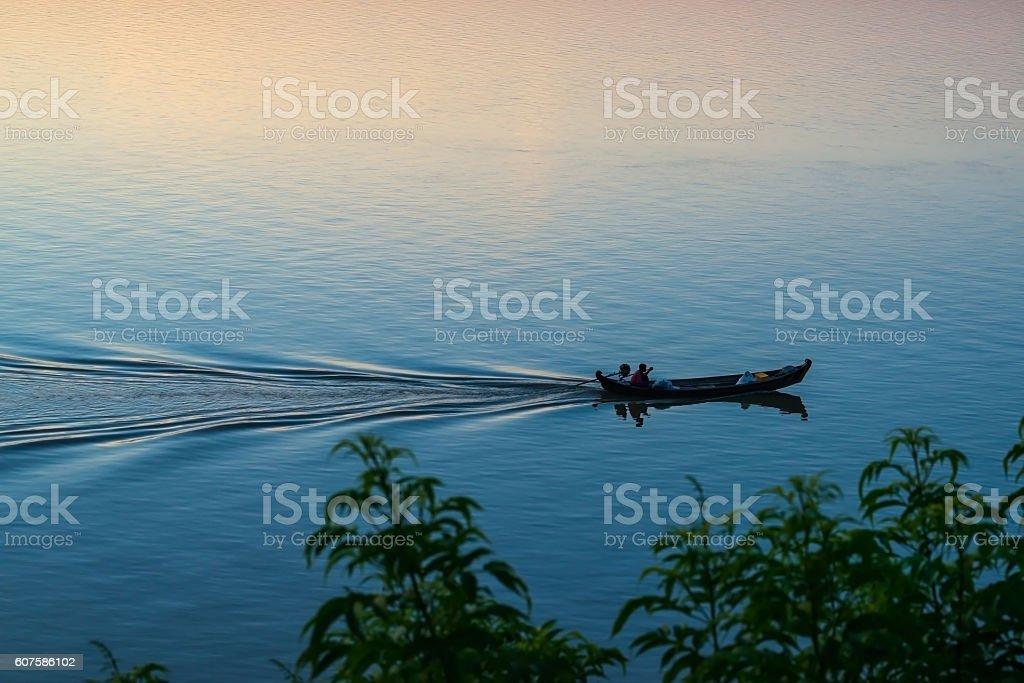 Fishermen in boat at sunset stock photo