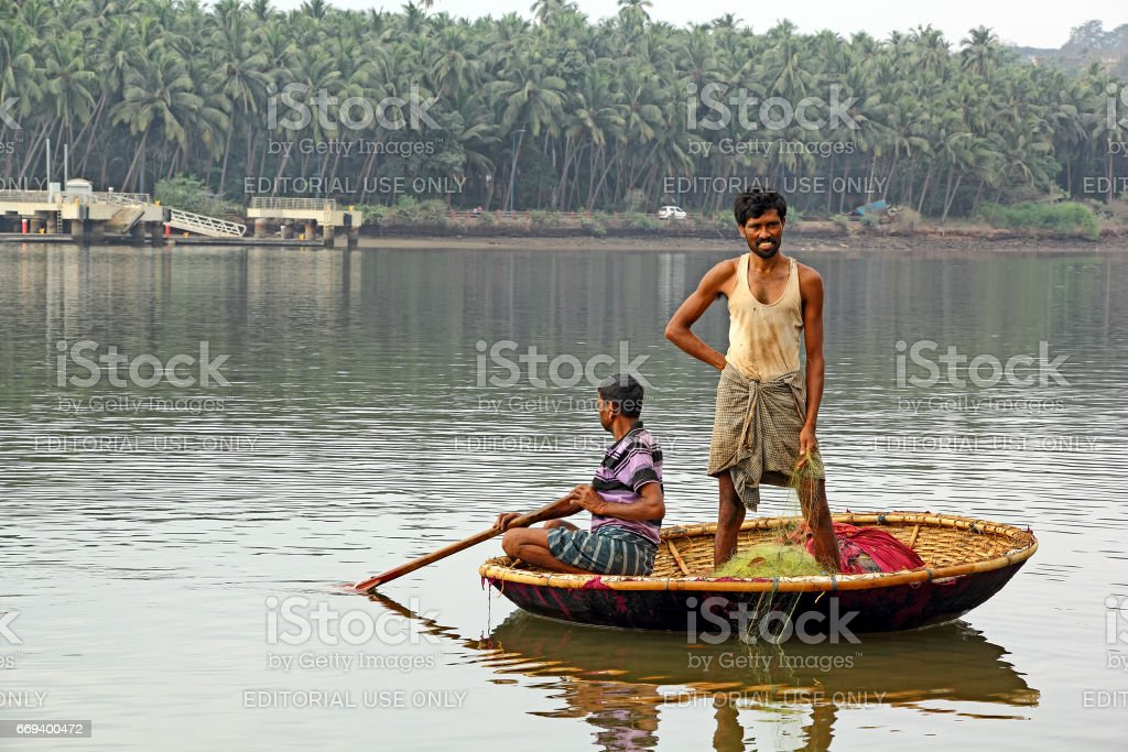Fishermen in Circular Boat Harvest Fish stock photo