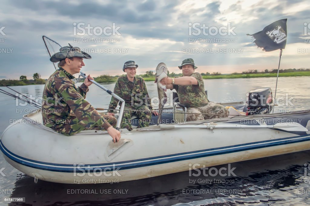 Fishermen in the boat catch fish stock photo