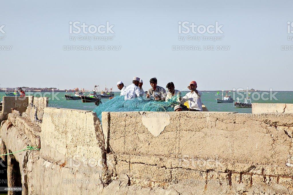 Fishermen mending nets at Bet Dwarka royalty-free stock photo