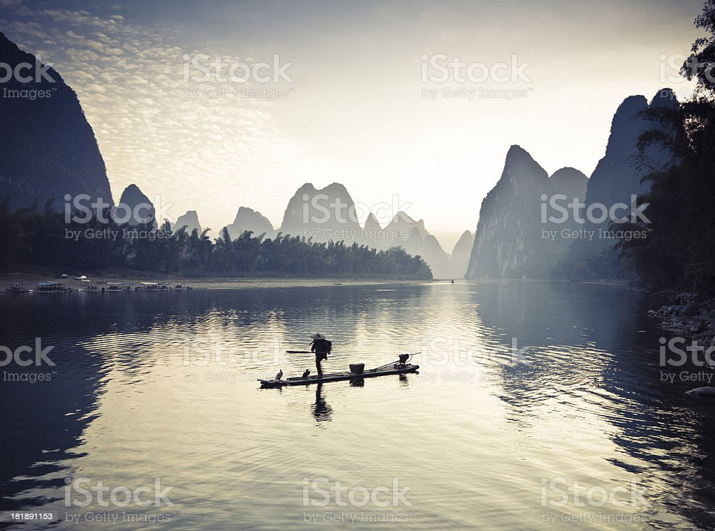 Fishermen on li river surrounded by mountains stock photo